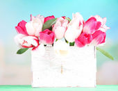 Beautiful tulips  in wooden box, on light background — Стоковое фото