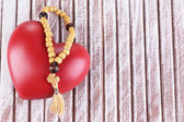 Heart with rosary beads on wooden background — Stock Photo