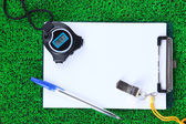 Sheet of paper and sports equipment on grass close-up — Stock Photo