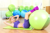 Young woman training with gymnastic ball in gym — Foto Stock