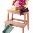 Wicker basket with flowers and fruits,  on small wooden ladder, isolated on white — Stock Photo #45070467