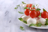Tasty mozzarella cheese with basil and tomatoes on plate, on wooden table — Stock Photo