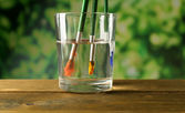 Brush with color paint in glass of water, on wooden table, on nature background — Foto de Stock