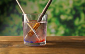 Brush with color paint in glass of water, on wooden table, on nature background — ストック写真