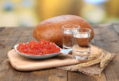 Composition with glasses of vodka  bread and red caviar on wooden table, on bright background — Stock Photo