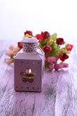 Decorative metallic lantern and artificial flowers on color wooden table, on light background — Stock Photo