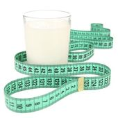 Glass of milk with measuring tape isolated on white — Stock Photo