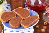Bread with sweet chocolate hazelnut spread on plate on table — Stock Photo