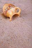 Greek ceramic amphora on sand, close up — Stockfoto