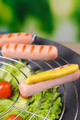 Grilled sausage in wok on bright background — Stock Photo