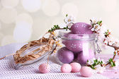Composition with Easter eggs in glass jar and blooming branches on light background — Zdjęcie stockowe
