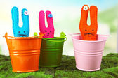 Funny handmade Easter rabbits in pails, on green grass — Stockfoto
