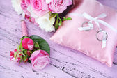 Beautiful wedding bouquet and cushion with rings on wooden background — Stock Photo