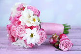 Beautiful wedding bouquet and boutonniere on table on bright background — Stock Photo
