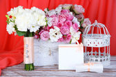 Beautiful wedding composition with flowers on table on fabric background  — Stock Photo