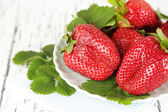 Strawberries with leaves on plate, on wooden background — Stock Photo