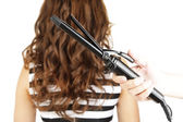 Stylist using curling iron for hair curls, close-up, isolated on white — Stock Photo