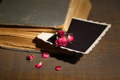 Old book with blank photo paper and beautiful pink dried roses on wooden background — Stock Photo