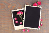 Blank photo paper and beautiful pink dried roses on wooden background — Stock fotografie