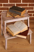 Books on wooden ladder on  color wall background — Stock Photo