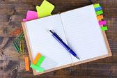 Cuaderno, pluma y pegatinas sobre fondo de madera — Foto de Stock
