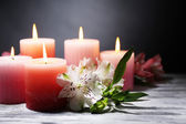 Beautiful candles with flowers on wooden table, on dark background — Stock Photo