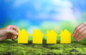 Hands hold houses on grass on natural background — Stock Photo