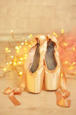 Ballet pointe shoes on floor on bokeh background — Stock Photo