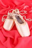 Ballet pointe shoes on red fabric background — Stock Photo