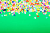 Confetti on green background — Stock Photo