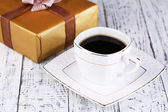 Cup of coffee and gift on wooden table close-up — Stock Photo