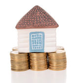 House standing on heap of coins isolated on white — Stock fotografie