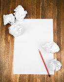 Sheet of white paper with crumpled  paper  and pencil on table close-up — Foto de Stock