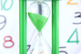 Hourglass on big clock  background — Stock Photo