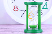 Hourglass and big clock on light background — Stock fotografie