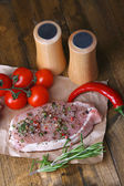 Raw meat steak with spices  herbs, on wooden background — Zdjęcie stockowe