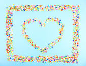 Confetti in shape of heart on blue background — Stock Photo