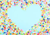 Confetti in shape of heart on blue background — Stockfoto