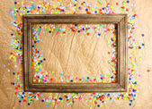 Photoframe with confetti on paper background — Stock Photo