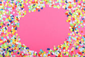 Confetti on pink background — Stock Photo