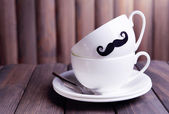 Cup with mustache on table on wooden background — Stock Photo