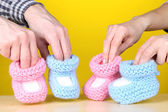 Hands with crocheted booties for baby, on color background — Stock Photo