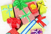 Many colorful presents with luxury ribbons  on color carpet background — Stock Photo