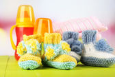 Composition with crocheted booties for baby,clothes, bottles on wooden background — Stock Photo
