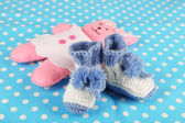 Crocheted booties for baby, on color background — Stock Photo