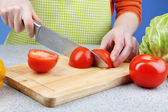 Female hands cutting tomato on wooden board, close-up — Zdjęcie stockowe