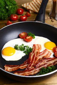 Scrambled eggs and bacon on frying pan on table close-up — Stock Photo
