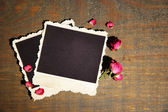 Blank photo paper and beautiful pink dried roses on wooden background — Foto de Stock