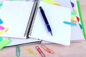 Cahier, stylo et autocollants sur fond en bois — Photo