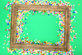 Photoframe with confetti on green background — Stock Photo
